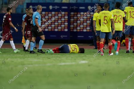 Colombia's Mateus Uribe, center, lies on the ground during a Copa America soccer match against Venezuela at the Olimpico stadium in Goiania, Brazil
