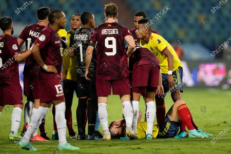 Colombia's Mateus Uribe, below, lies on the ground during a Copa America soccer match against Venezuela at the Olimpico stadium in Goiania, Brazil