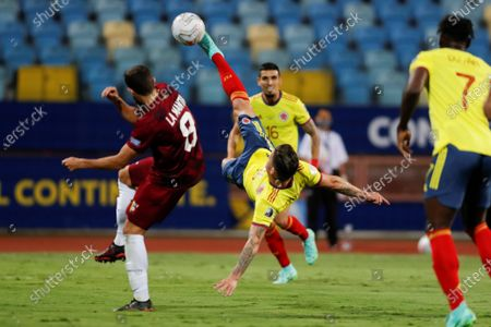 Colombia's Mateus Uribe (C) shoots before the defense of Venezuela's Francisco La Mantia during the Copa America 2021 group B soccer match between Colombia and Venezuela at the Pedro Ludovico Teixeira Olympic Stadium, in Goiania, Brazil, 17 June 2021.