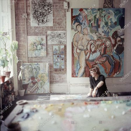 View of American painter Nell Blaine (1922 - 1996) as she sits on the floor of her studio, New York, New York, 1957.