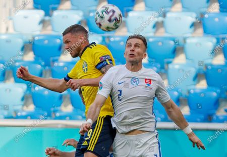 Sweden's Marcus Berg, left, and Slovakia's Peter Pekarik compete to head the ball during the Euro 2020 soccer championship group E match between Sweden and Slovakia at Saint Petersburg Stadium in St. Petersburg, Russia