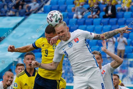 Slovakia's Ondrej Duda, right, and Sweden's Marcus Berg fight an aerial duel during the Euro 2020 soccer championship group E match between Sweden and Slovakia, at the Saint Petersburg stadium, in Saint Petersburg, Russia