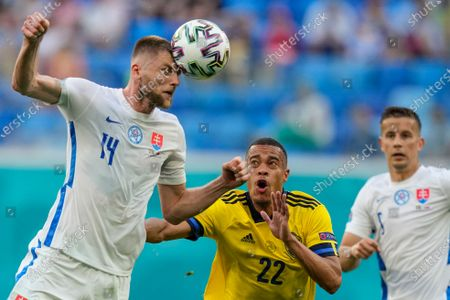 Slovakia's Milan Skriniar heads the ball as Sweden's Robin Quaison looks, during the Euro 2020 soccer championship group E match between Sweden and Slovakia, at the Saint Petersburg stadium, in Saint Petersburg, Russia