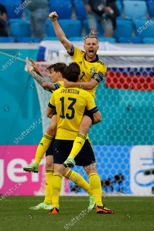 Sweden's Sebastian Larsson, top, and Sweden's Gustav Svensson celebrate at the end of the Euro 2020 soccer championship group E match between Sweden and Slovakia, at the Saint Petersburg stadium, in Saint Petersburg, Russia, . Sweden won 1-0