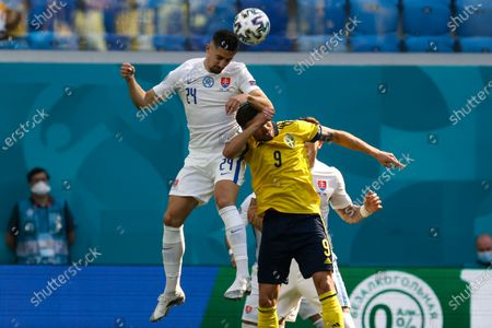 Slovakia's Martin Koscelnik heads the ball past Sweden's Marcus Berg during the Euro 2020 soccer championship group E match between Sweden and Slovakia, at the Saint Petersburg stadium, in Saint Petersburg, Russia