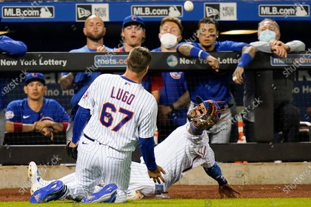 Chicago Cubs players watch as New York Mets' Jonathan Villar, right, and relief pitcher Seth Lugo attempt to catch a foul ball by Anthony Rizzo during the ninth inning of a baseball game, in New York