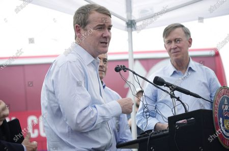 """Sen. Michael Bennet, D-Colo., foreground, makes a point as U.S. Department of Health and Human Services Secretary Xavier Becerra, background left, and U.S. Sen. John Hickenlooper, D-Colo., look on during a visit to a pair of buses set up as traveling clinics as part of the state's """"Vaccines For All"""" campaign, in Aurora, Colo. The buses are being used to distribute the COVID-19 vaccines"""