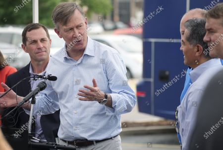 """Sen. John Hickenlooper, D-Colo., center, speaks to Department of Health and Human Services Secretary Xavier Becerra, right, as U.S. Rep. Jason Crow, D-Colo., looks on during a visit to a pair of buses set up as traveling clinics as part of the state's """"Vaccines For All"""" campaign, in Aurora, Colo. The buses are being used to distribute the COVID-19 vaccines"""