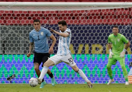 Argentina's Lionel Messi, center, goes with the ball as Uruguay's Jose Gimenez challenges him during a Copa America soccer match at the National Stadium in Brasilia Brazil