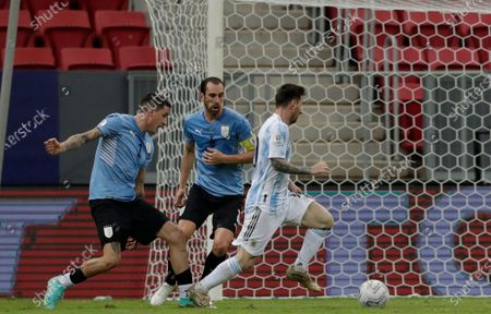 Argentina's Lionel Messi, right, dribbles past Uruguay's Jose Gimenez, left, and Diego Godin during a Copa America soccer match at the National Stadium in Brasilia Brazil