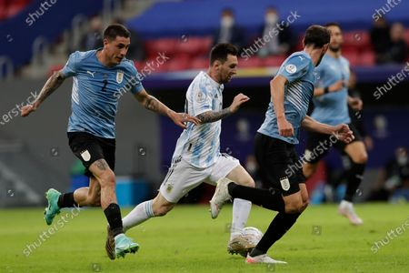 Argentina's Lionel Messi, center, dribbles past Uruguay's Jose Gimenez, left, during a Copa America soccer match at the National Stadium in Brasilia Brazil