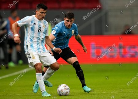 Argentina's Marcos Acuna, left, is challenged by Uruguay's Giovanni Gonzalez during a Copa America soccer match at National stadium in Brasilia, Brazil