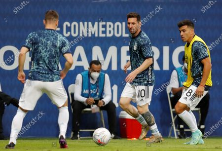 Argentina's Lionel Messi (C) and Marcos Acuna (R) warm prior to the Copa America group B soccer match between Argentina and Uruguay at the Mane Garrincha Stadium in Brasilia, Brazil, 18 June 2021.
