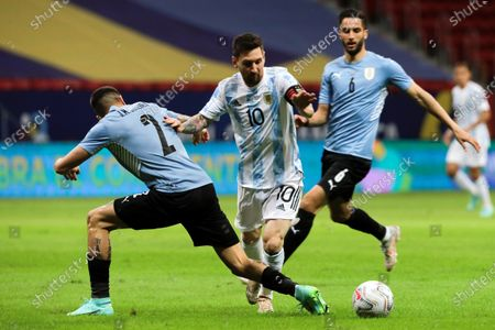 Argentina's Lionel Messi (C) in action against Uruguay's Jose Gimenez (L) during the Copa America group B soccer match between Argentina and Uruguay at the Mane Garrincha Stadium in Brasilia, Brazil, 18 June 2021.