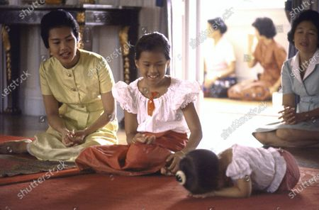 Thailand's Queen Sirikit (L) leading her daughter Princess Ubolratana (C) through ritual of Sai Bat, giving alms to Buddhist priests done on one's birthday; at Chitralada Palace. (The other girl is prob. daughter Chulabhorn).
