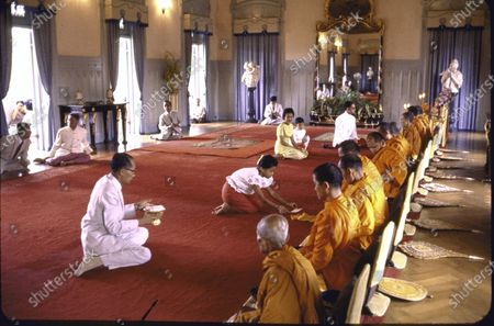 Thailand's Queen Sirikit (C 3L) leading her daughter Princess Ubolratana (C) through ritual of Sai Bat, the giving of alms to Buddhist priests on one's birthday; at Chitralada Palace.