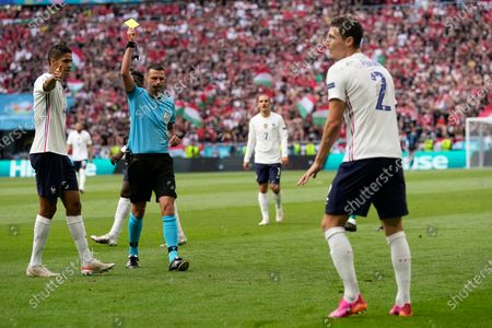 British referee Michael Oliver shows a yellow card to France's Benjamin Pavard, right, during the Euro 2020 soccer championship group F match between Hungary and France, at the Ferenc Puskas stadium in Budapest