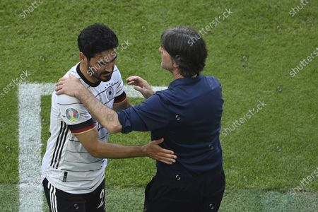 Germany's manager Joachim Loew, right, greets Germany's Ilkay Gundogan after is substituted during the Euro 2020 soccer championship group F match between Portugal and Germany at the football arena stadium in Munich