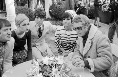 English model and actress Twiggy sitting and talking with her manager and boyfriend Justin de Villeneuve, American actor Steve McQueen and American pop music duo Sonny and Cher at a party held in her honor in Beverly Hills on 30th April, 1967.