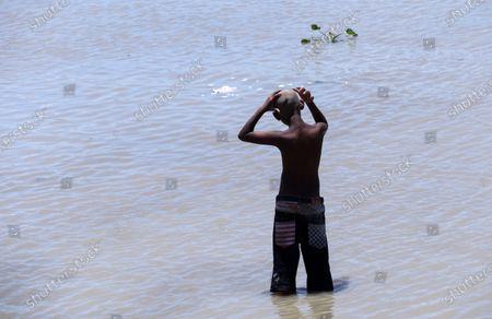A boy takes bath  in the Brahmaputra river after tonsure his hair on June 16, 2021 in Guwahati, India. Shaving hair or tonsuring hair is practiced by Hinduism after death of a family member and completing the last rites (Sraddha).