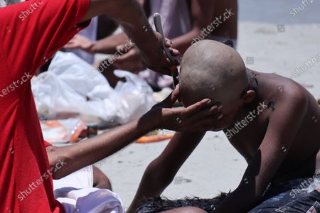 A boy tonsure his hair on the banks of Brahmaputra river on June 16, 2021 in Guwahati, India. Shaving hair or tonsuring hair is practiced by Hinduism after death of a family member and completing the last rites (Sraddha).
