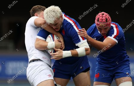 Joshua Brennan of France is tackled by Jack Clement of England.