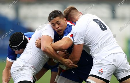 Connor Sa of France is tackled by Archie Vanes and Jack Clement of England.