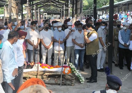 """Union Sports Minister Kiren Rijiju paying last respects to Milkha Singh during his funeral at the cremation ground in Sector 25, on June 19, 2021 in Chandigarh, India. Milkha Singh died on Friday of complications due to coronavirus disease (Covid-19), at the age of 91, after a month-long battle with Covid-19 in Chandigarh. Milkha, famously known by the sobriquet 'Flying Sikh', had contracted the viral contagion last month and was admitted to the Intensive Care Unit (ICU) of a top hospital in Chandigarh due to """"dipping levels of oxygen""""."""
