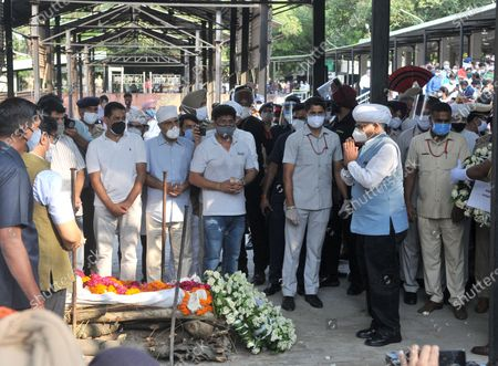 """Punjab Governor VP Singh Bhadnore paying last respects to Milkha Singh during his funeral at the cremation ground in Sector 25, on June 19, 2021 in Chandigarh, India. Milkha Singh died on Friday of complications due to coronavirus disease (Covid-19), at the age of 91, after a month-long battle with Covid-19 in Chandigarh. Milkha, famously known by the sobriquet 'Flying Sikh', had contracted the viral contagion last month and was admitted to the Intensive Care Unit (ICU) of a top hospital in Chandigarh due to """"dipping levels of oxygen""""."""