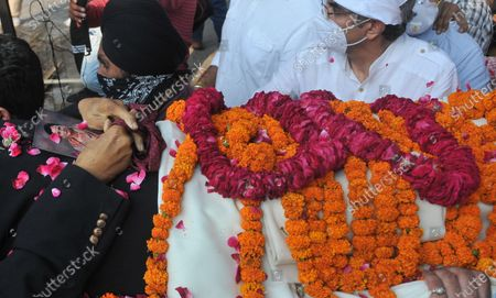 """A photograph of his wife Nirmal Kaur is seen placed in Milkha Singh's hands as his body is taken for last rites at the cremation ground in Sector 25, on June 19, 2021 in Chandigarh, India. Milkha Singh died on Friday of complications due to coronavirus disease (Covid-19), at the age of 91, after a month-long battle with Covid-19 in Chandigarh. Milkha, famously known by the sobriquet 'Flying Sikh', had contracted the viral contagion last month and was admitted to the Intensive Care Unit (ICU) of a top hospital in Chandigarh due to """"dipping levels of oxygen""""."""
