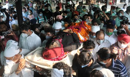 """Legendary Indian sprinter Milkha Singh's body being taken for last rites at the cremation ground in Sector 25, on June 19, 2021 in Chandigarh, India. Milkha Singh died on Friday of complications due to coronavirus disease (Covid-19), at the age of 91, after a month-long battle with Covid-19 in Chandigarh. Milkha, famously known by the sobriquet 'Flying Sikh', had contracted the viral contagion last month and was admitted to the Intensive Care Unit (ICU) of a top hospital in Chandigarh due to """"dipping levels of oxygen""""."""