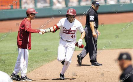 Stanford's Christian Robinson, right, shakes hands with third base coach Tommy Nicholson while rounding the bases after hitting a two-run home run against North Carolina State in the seventh inning in the opening baseball game of the College World Series, at TD Ameritrade Park in Omaha, Neb