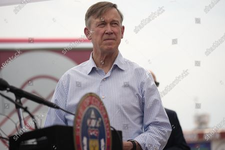 """Senator John Hickenlooper, D-Colo., waits to speak during a visit to a pair of buses set up as travelling clinics as part of the state's Vaccines For All"""" campaign, in Aurora, Colo. The buses are being used to distribute the COVID-19 vaccines to a majority of adults"""