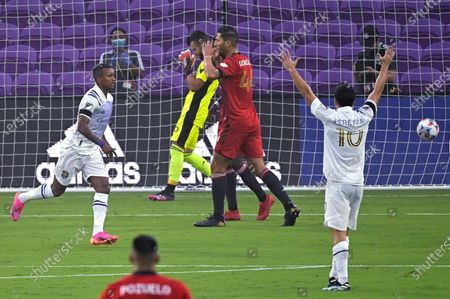 Toronto FC goalkeeper Quentin Westberg (16) and defender Omar Gonzalez (44) react after Orlando City forward Nani, left, scored a goal. while midfielder Mauricio Pereyra (10) celebrates during the first half of an MLS soccer match, in Orlando, Fla