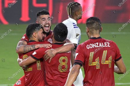 Toronto FC midfielder Jonathan Osorio (21) is congratulated by midfielder Alejandro Pozuelo, second from left, midfielder Mark Delgado (8) and defender Omar Gonzalez (44) after Osorio scored a goal during the first half of the team's MLS soccer match against Orlando City, in Orlando, Fla