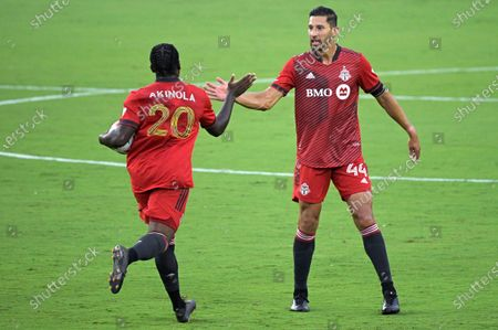 Toronto FC forward Ayo Akinola (20) is congratulated by defender Omar Gonzalez (44) after Akinola scored a goal during the first half of the team's MLS soccer match against Orlando City, in Orlando, Fla