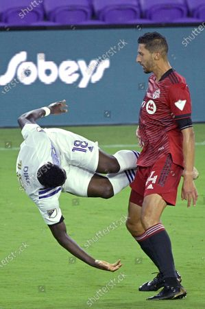 Orlando City forward Daryl Dike (18) flips through the air after colliding with Toronto FC defender Omar Gonzalez, right, during the second half of an MLS soccer match, in Orlando, Fla. Gonzalez received a yellow card after the collision