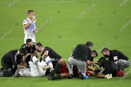 Trainers attend to Orlando City forward Daryl Dike, left, and Toronto FC defender Omar Gonzalez, right, after they collided while going for a head ball during the second half of an MLS soccer match, in Orlando, Fla