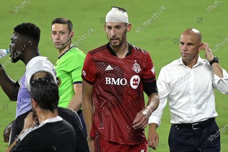 Toronto FC defender Omar Gonzalez, second from right, leaves the pitch with coach Chris Armas, right, after Gonzalez was injured while going for a header against Orlando City forward Daryl Dike, left, during the second half of an MLS soccer match, in Orlando, Fla