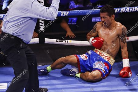 Michael Dasmarinas of the Philippines falls for the second time holding his right flank during his fight against Naoya Inoue of Japan, a 12 round WBA/IBF Bantamweight Title fight at The Theater at Virgin Hotels in Las Vegas, Nevada, USA, 19 June 2021.