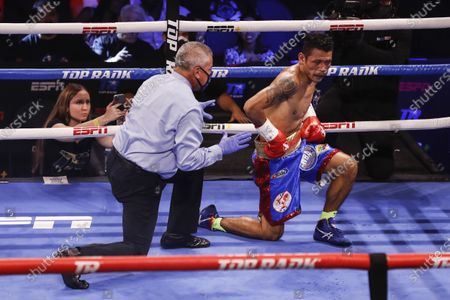 Stock Picture of Michael Dasmarinas of the Philippines falls for the second time holding his right flank during his fight against Naoya Inoue of Japan, a 12 round WBA/IBF Bantamweight title fight at The Theater at Virgin Hotels in Las Vegas, Nevada, USA, 19 June 2021.