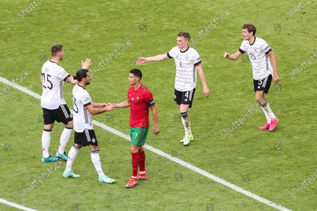 Stock Picture of (210620) - MUNICH, June 20, 2021 (Xinhua) - Thomas Mueller (1st R), Matthias Ginter (2nd R) and Niklas Suele (1st L) of Germany celebrate victory as Emre Can (2nd L) of Germany and Cristiano Ronaldo of Portugal greet other after the UEFA Euro 2020 Championship Group F match in each of Munich, Germany, June 19, 2021.