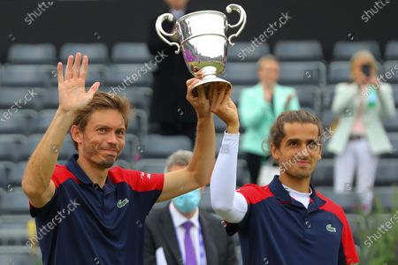 France's Pierre-Hugues Herbert (R) and France's Nicolas Mahut (L) celebrate with the trophy after winning the mens doubles final against United States of America's Reilly Opelka and Australia's John Peers during their finals match at the Cinch Championships at the Queen's Club in London, Britain, 20 June 2021.