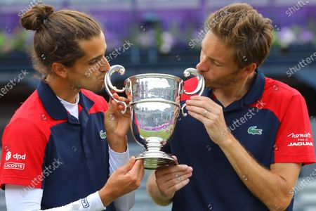 France's Pierre-Hugues Herbert (L) and France's Nicolas Mahut (R) celebrate with the trophy after winning the mens doubles final against United States of America's Reilly Opelka and Australia's John Peers during their finals match at the Cinch Championships at the Queen's Club in London, Britain, 20 June 2021.