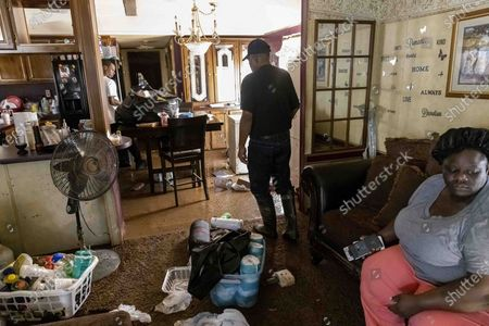 Percy Ross, center, the owner, works through his flood-damaged home as his son, Michael Roberts, left, seeks to recover valuables after heavy flooding Saturday night, in Northport, Ala., . At right is Ross's daughter, Candy Roberts