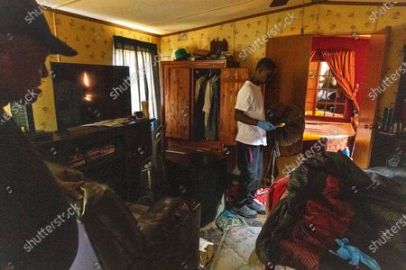 Stock Picture of Percy Ross, left, the owner, watches his son, Michael Roberts, search Ross's flood-damaged home, after the heavy flooding Saturday in Northport, Ala