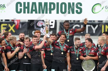 Saracens captain Owen Farrell and departing player Michael Rhodes lift the Greene King IPA Championship Trophy surrounded by teammates