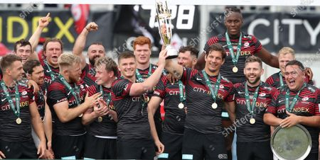 Stock Picture of Saracens captain Owen Farrell and departing player Michael Rhodes lift the Greene King IPA Championship Trophy surrounded by teammates
