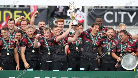 Stock Image of Saracens captain Owen Farrell and departing player Michael Rhodes lift the Greene King IPA Championship Trophy surrounded by teammates