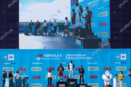 Swiss Edoardo Mortara (C), first place, German Pascal Wehrlein (C-L), second place and Neo Zealand Nick Cassidy (C-R), third place, stand on the podium after the second race of Formula E championship, at Miguel E. Abedin racecar in the state of Puebla, Mexico, 20 June 2021.
